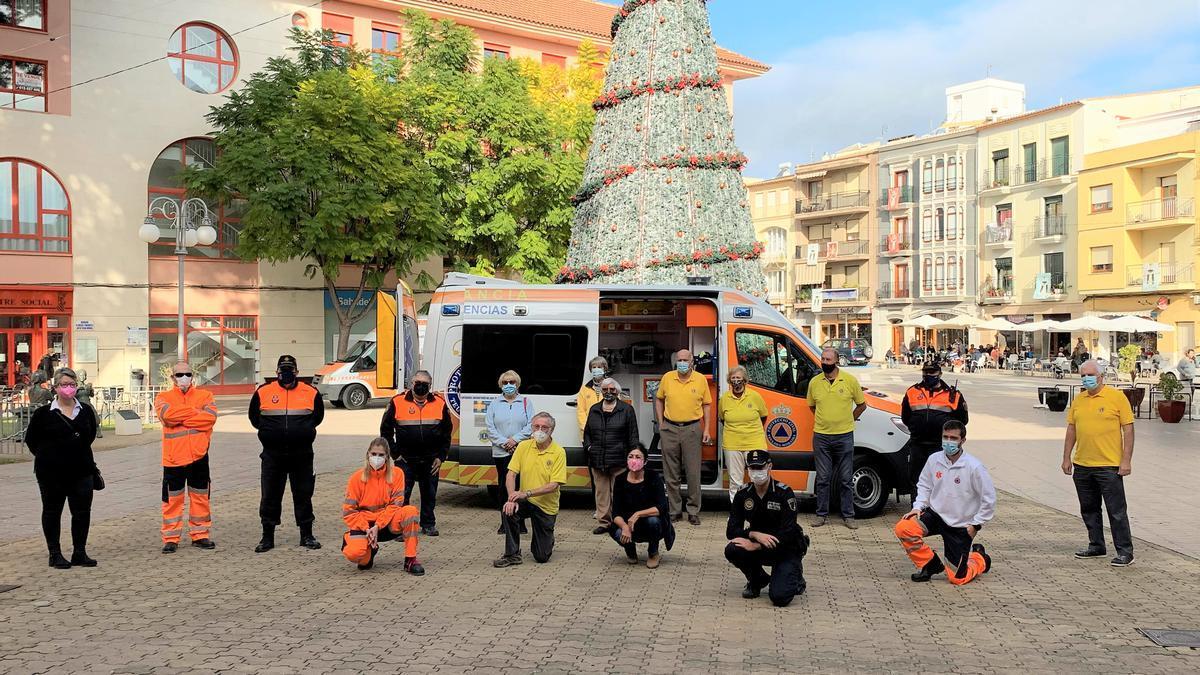 Los voluntarios de Proteccion Civil, la alcaldesa y representantes de la policía y de entidades solidarias posan delante de la ambulancia