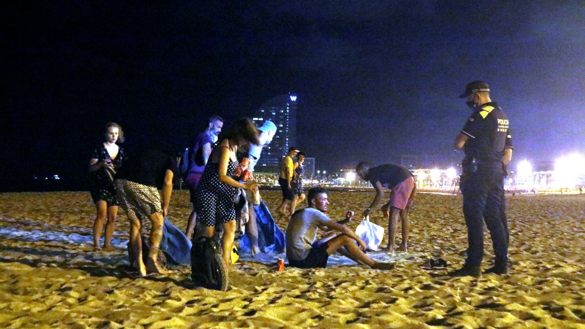 Un agent de policia desallotjant un grup de persones a la platja de la Barceloneta, a Barcelona.