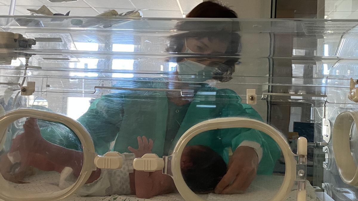 Una enfermera atiende a un bebé en el hospital Reina Sofía.