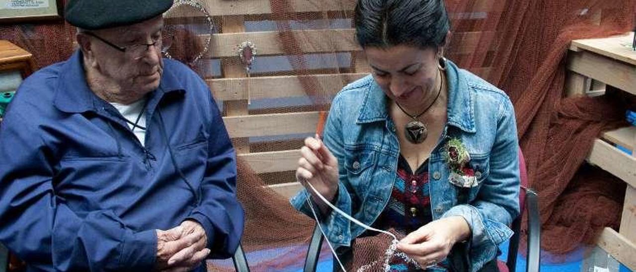 El veterano redero José Viña enseña a coser redes a la aprendiz Ángeles Sánchez.