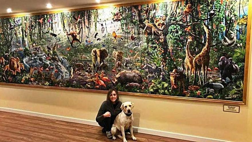 La joven toresana María de Mena posa con su perro junto al puzle que recrea la selva y que exhibe en un bastidor colgado en una pared del salón de su vivienda.
