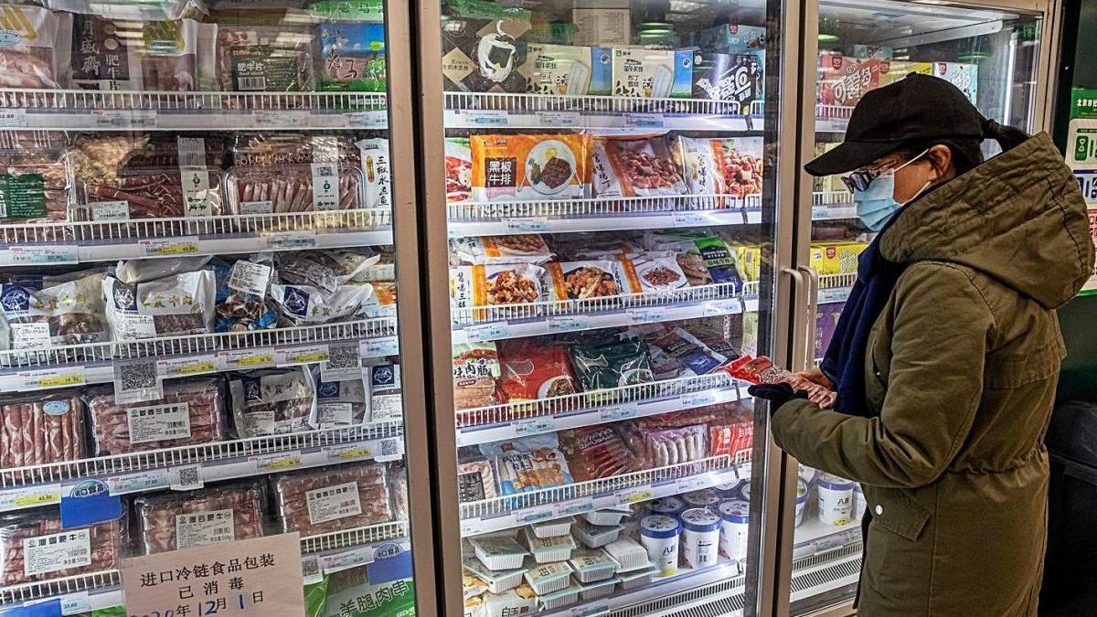 Una dona davant d?un congelador en un establiment de Pequín