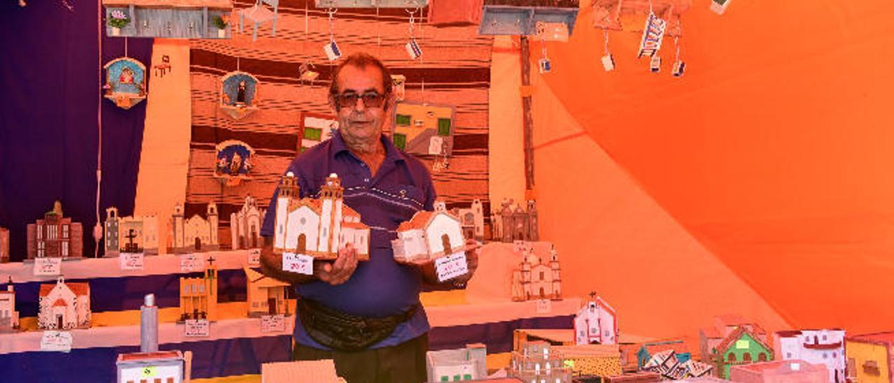 Manuel Sánchez, que lleva más de 30 años haciendo en su taller iglesias y casas de madera, en un puesto de la feria de artesanía de Vecindario.