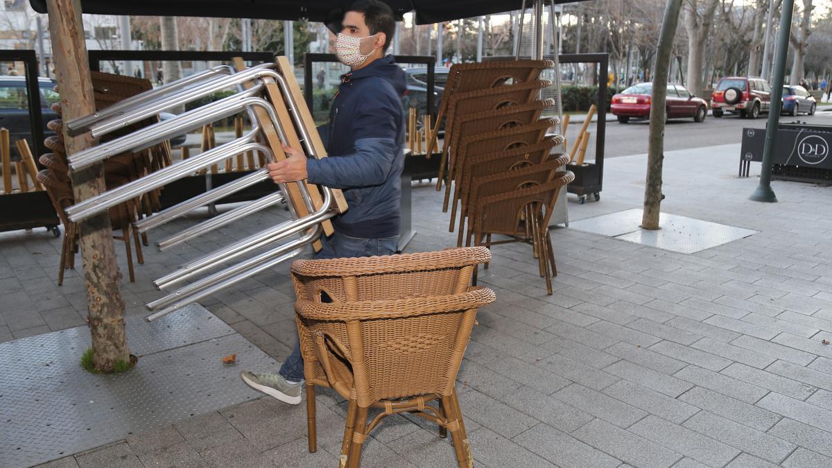 Un hombre recoge las mesas y sillas de una terraza de Palencia.