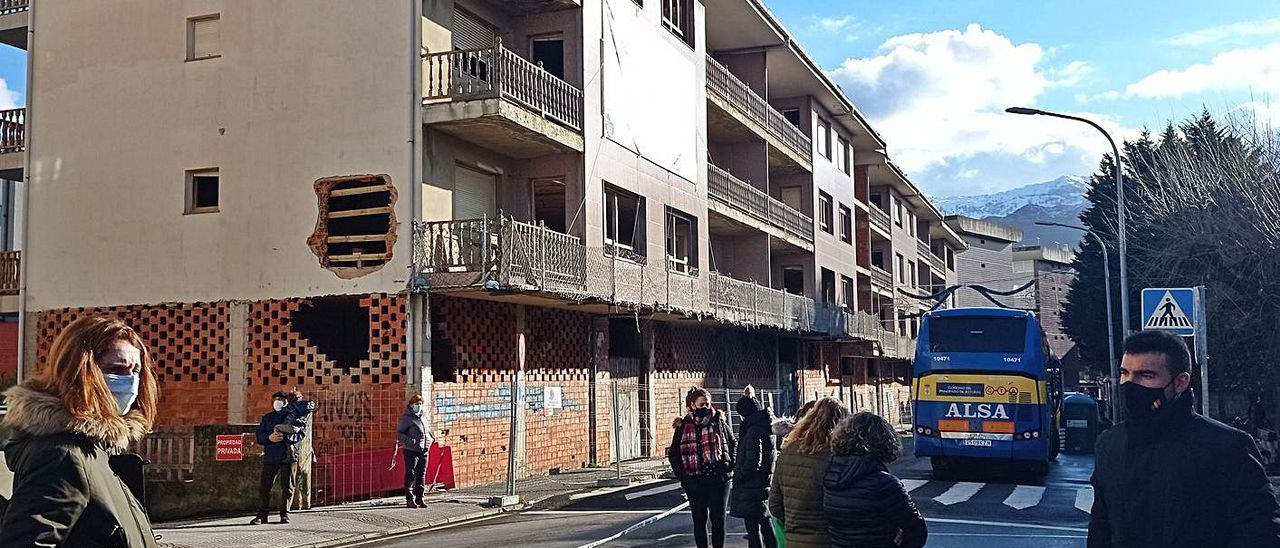 Varios padres esperan a la salida del colegio a sus hijos, junto al edificio de Celso Amieva en obras.   E. S. R.