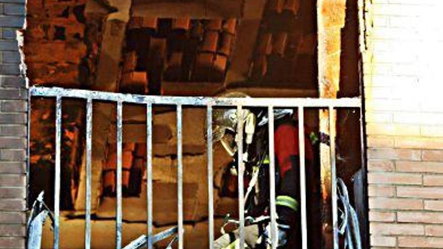 Un bombero trabaja en el interior del piso calcinado.