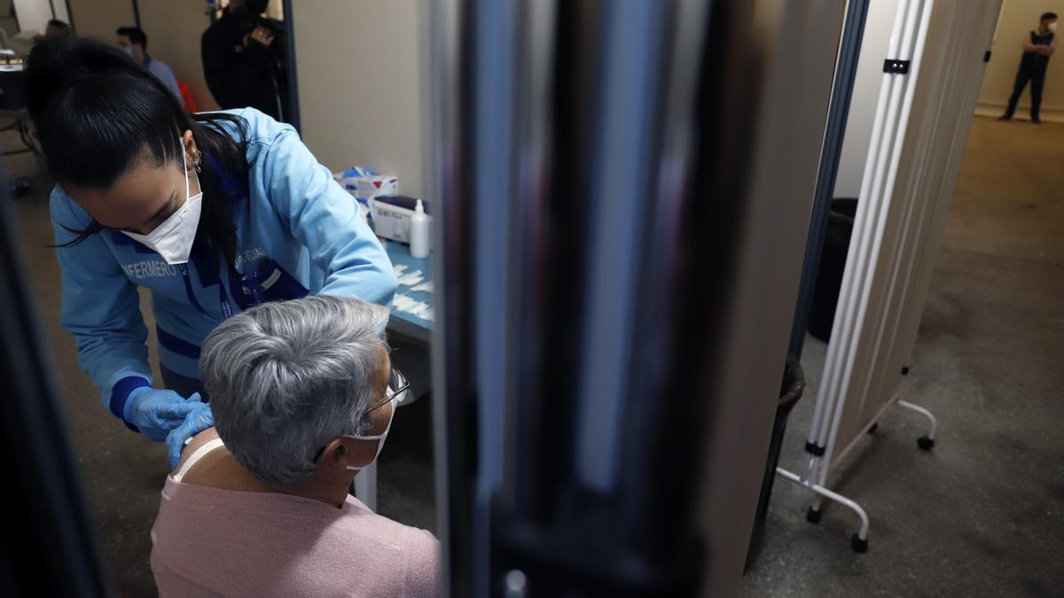 Una mujer recibe una vacuna frente al COVID.