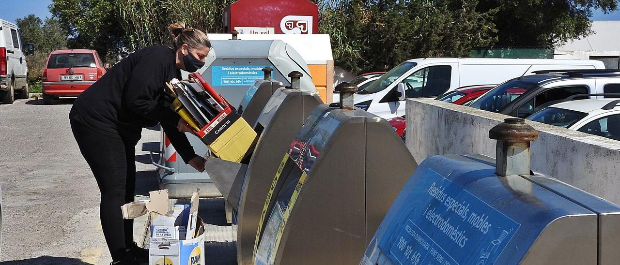 Una vecina deposita cajas de cartón en el correspondiente contenedor, en Sant Francesc.   C.C.