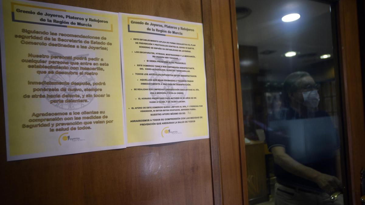 Carteles en la puerta de una joyería de Murcia donde se alude a esta medida.