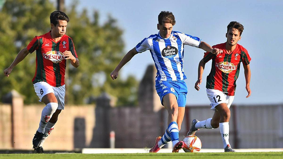 El delantero juvenil Noel, entre dos rivales del Racing Villalbés. |  // RCD