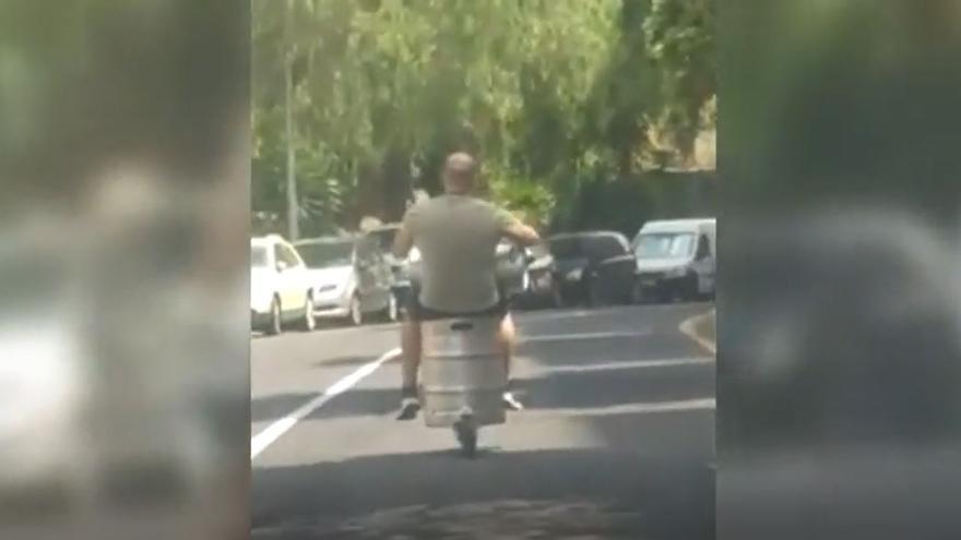 Un hombre conduce su patinete sobre un barril de cerveza en Santa Cruz