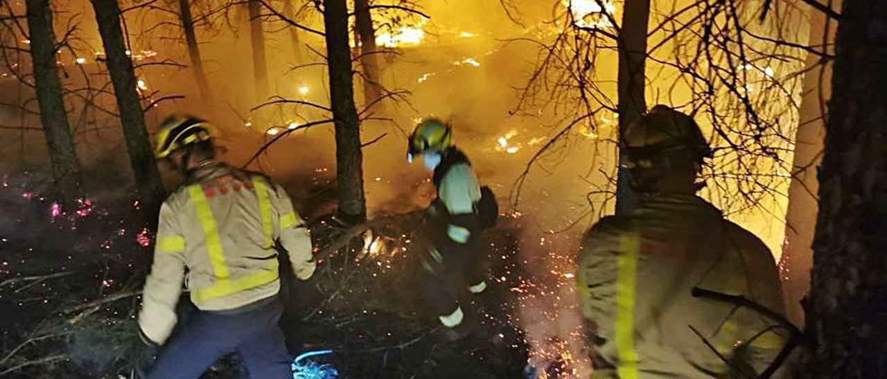 Miembros de los equipos de Bomberos, entre las llamas durante las labores de extinción.   Bomberos de Cataluña
