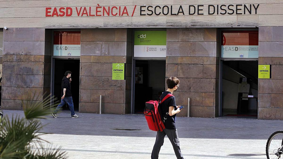 Dos jóvenes pasan por delante de las instalaciones de la EASD de València. | MIGUEL ÁNGEL MONTESINOS