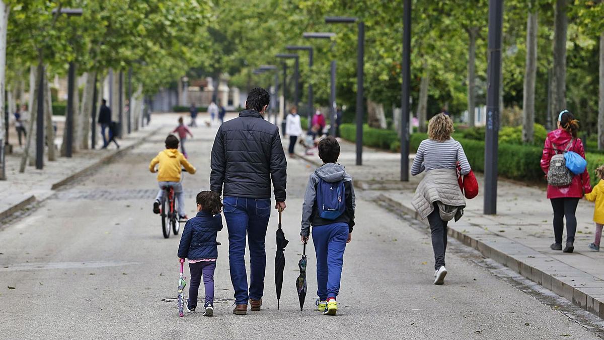 Un padre pasea con sus dos hijos por un parque. | A. Cámara - Europa Press