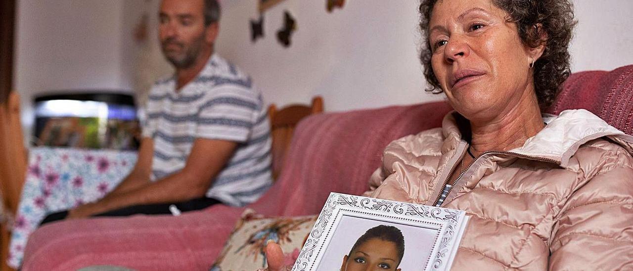 Sonia Padilla con una foto de Vanessa, asesinada presuntamente por su primo Jonatan en 2018. Al fondo, su marido Mauro.