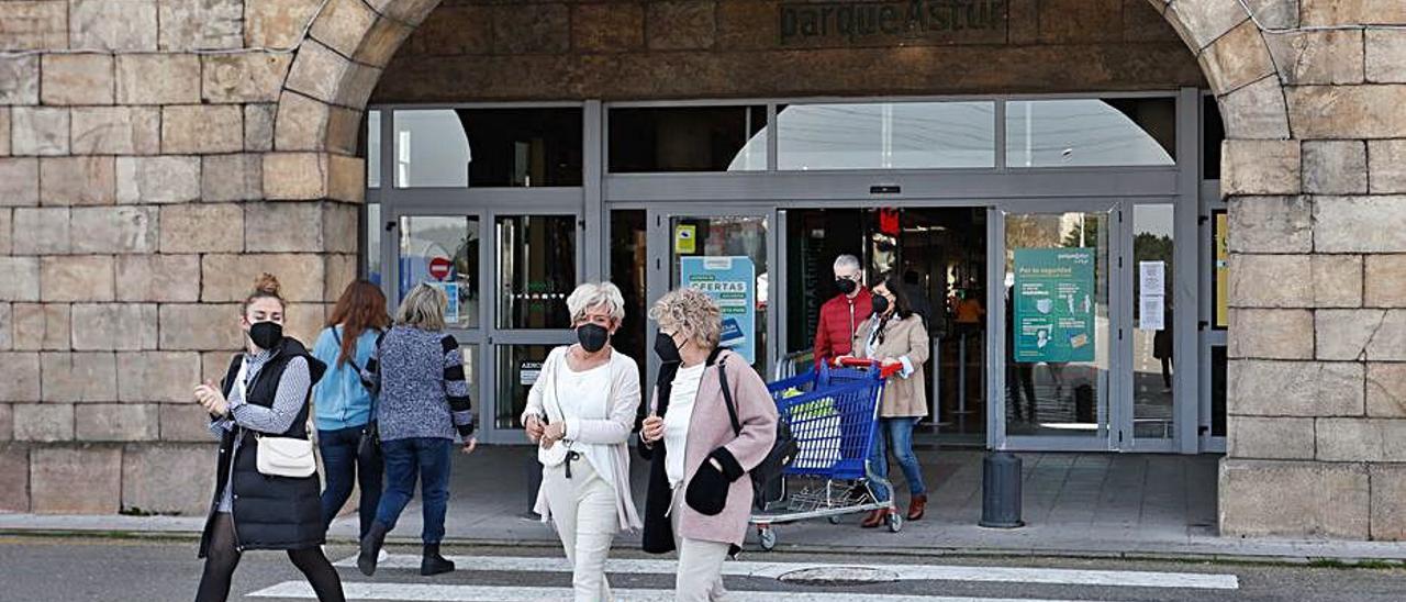 Arriba, aparcamiento del centro comercial. Sobre estas líneas, clientes a la salida de las instalaciones.