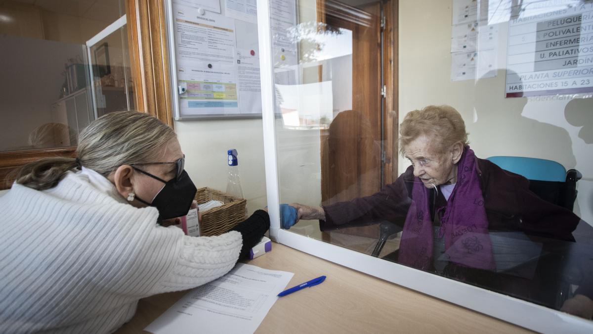 Dos familiares se tocan las manos en una visita en un centro de L'Eliana, en Valencia.