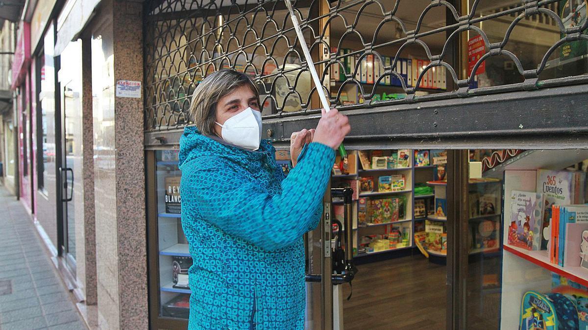 Conchi Conde, comerciante y presidenta de ProLimia, escenifica el cierre del comercio a las 18.00 horas en Xinzo. |   // IÑAKI OSORIO