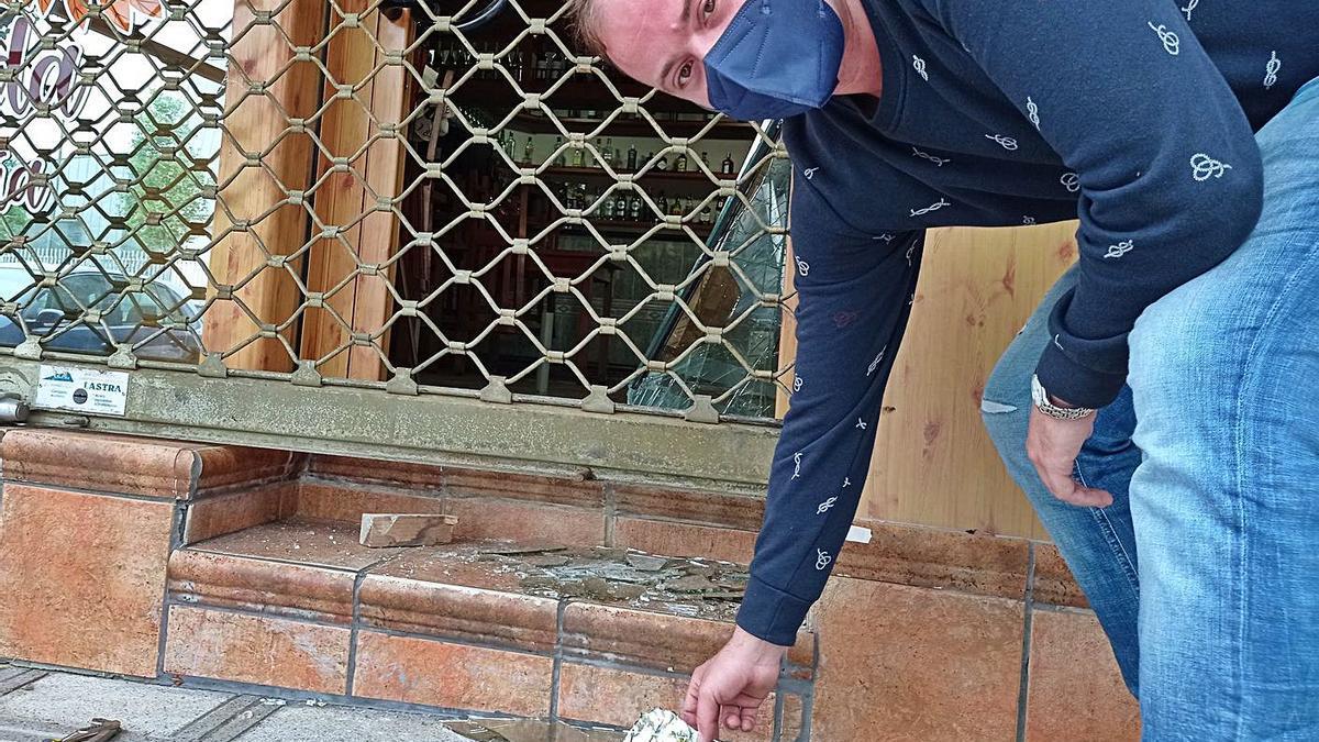 David Iglesias enseña los cristales rotos de la puerta de su sidrería, ayer, en Pola de Siero. | A. I.