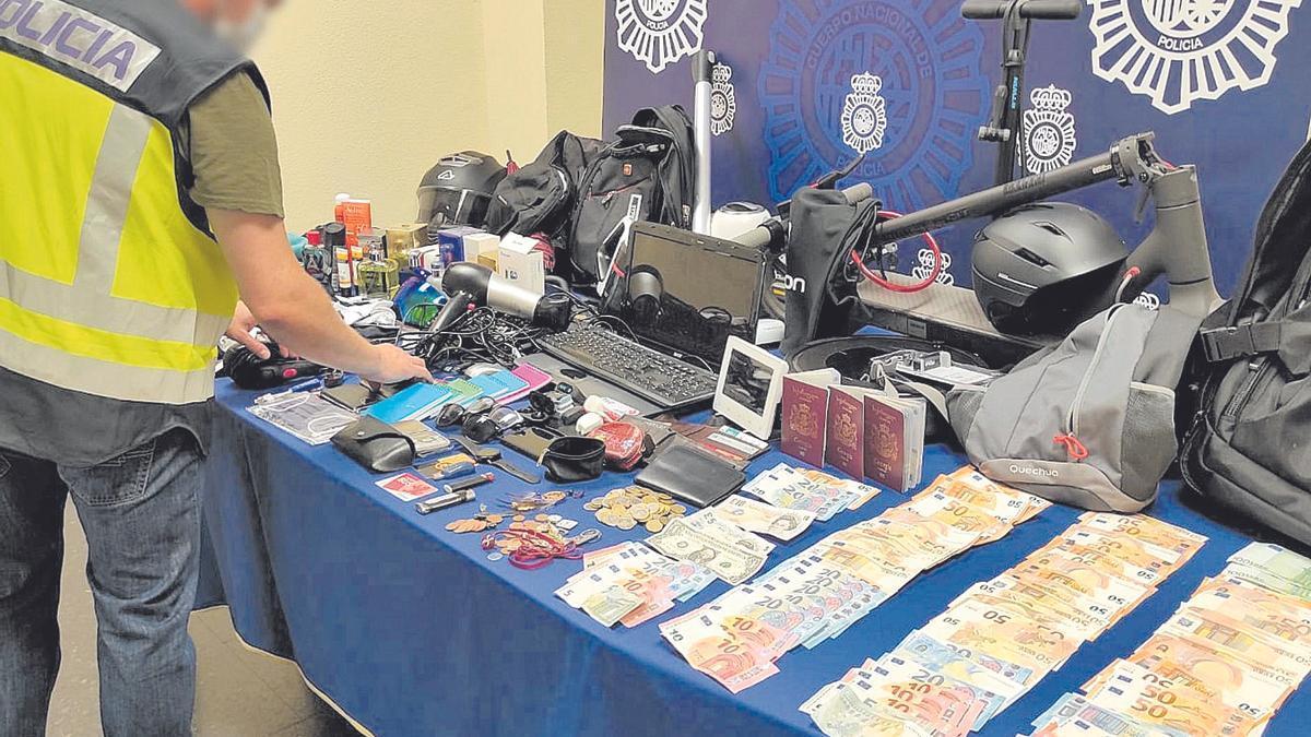 Un agente de la Policía Nacional repasa todo los objetos y dinero intervenido a la banda organizada la pasada semana.