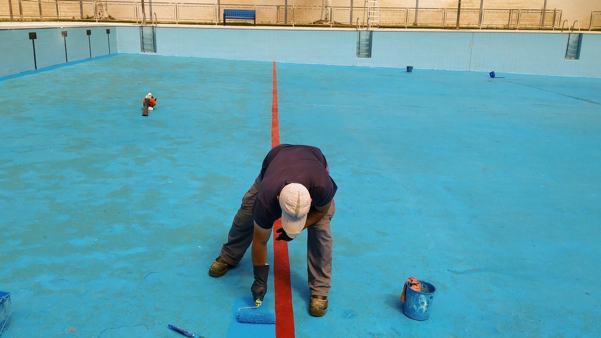 Un operario pinta el vaso principal de la piscina municipal