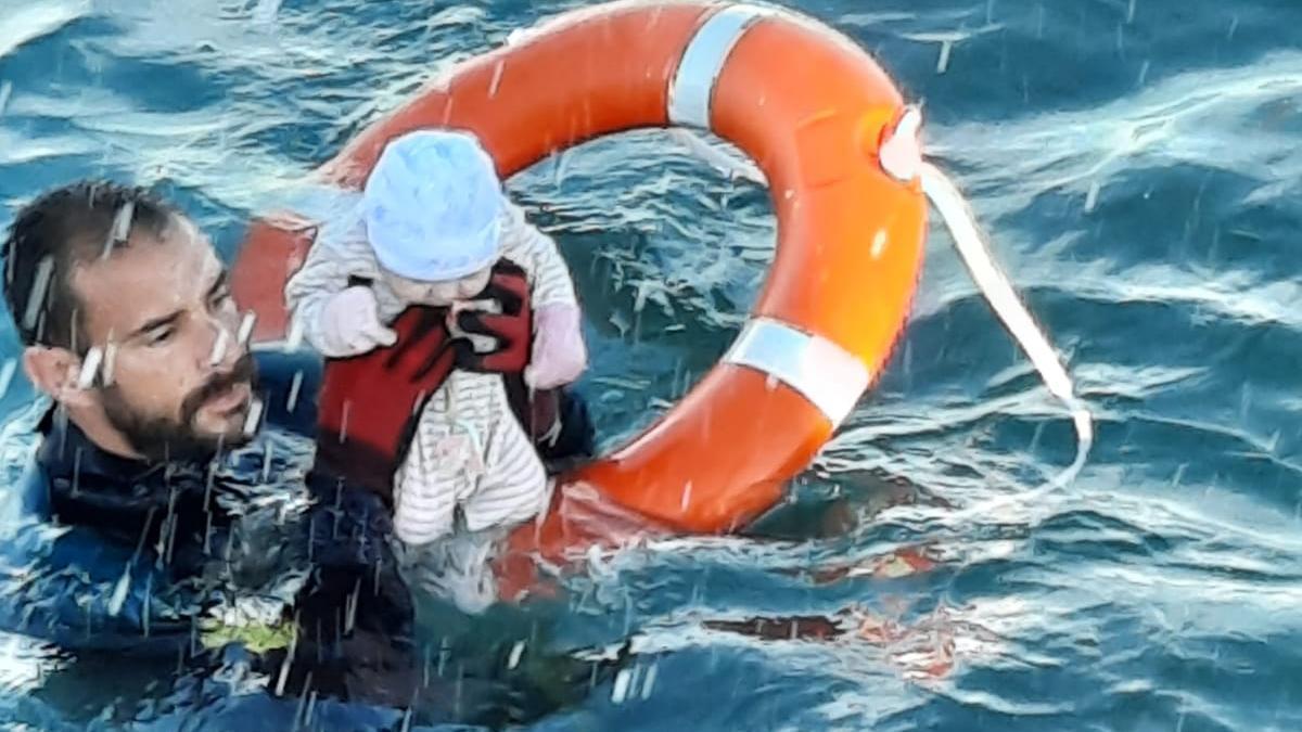 Un guardia givil rescatando a una bebé del mar.