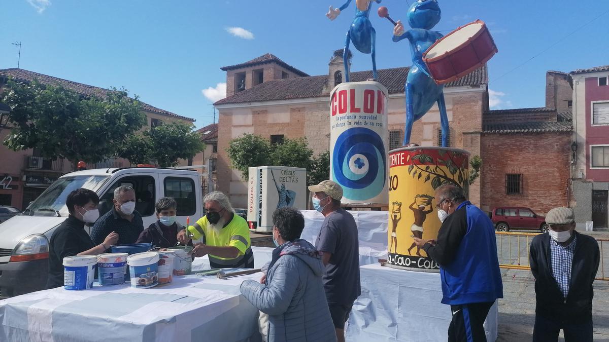 Los socios preparan la pintura para decorar la obra que será prendida en La Glorieta