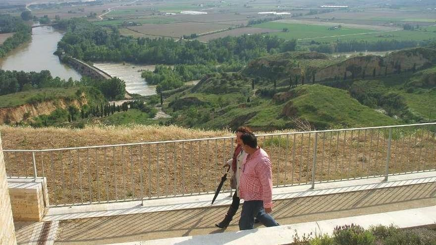 Dos personas pasean por el mirador desde el que se puede admirar el entorno del puente de piedra.