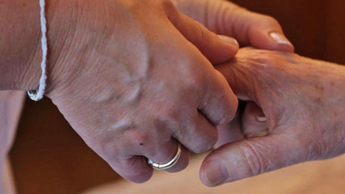 Una cuidadora masajea la mano de una persona mayor.