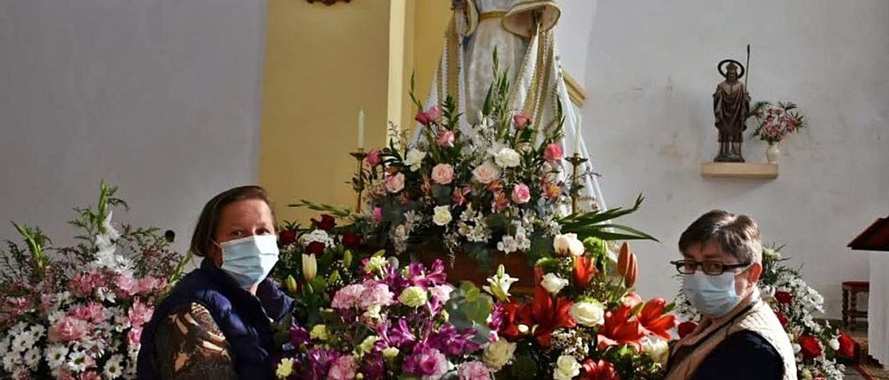 María Dolores Tomás (a la izquierda) y Ana Isabel Serdio, ante la Virgen, con los numerosos ramos de flores llegados a la parroquia. | Vicente Alonso