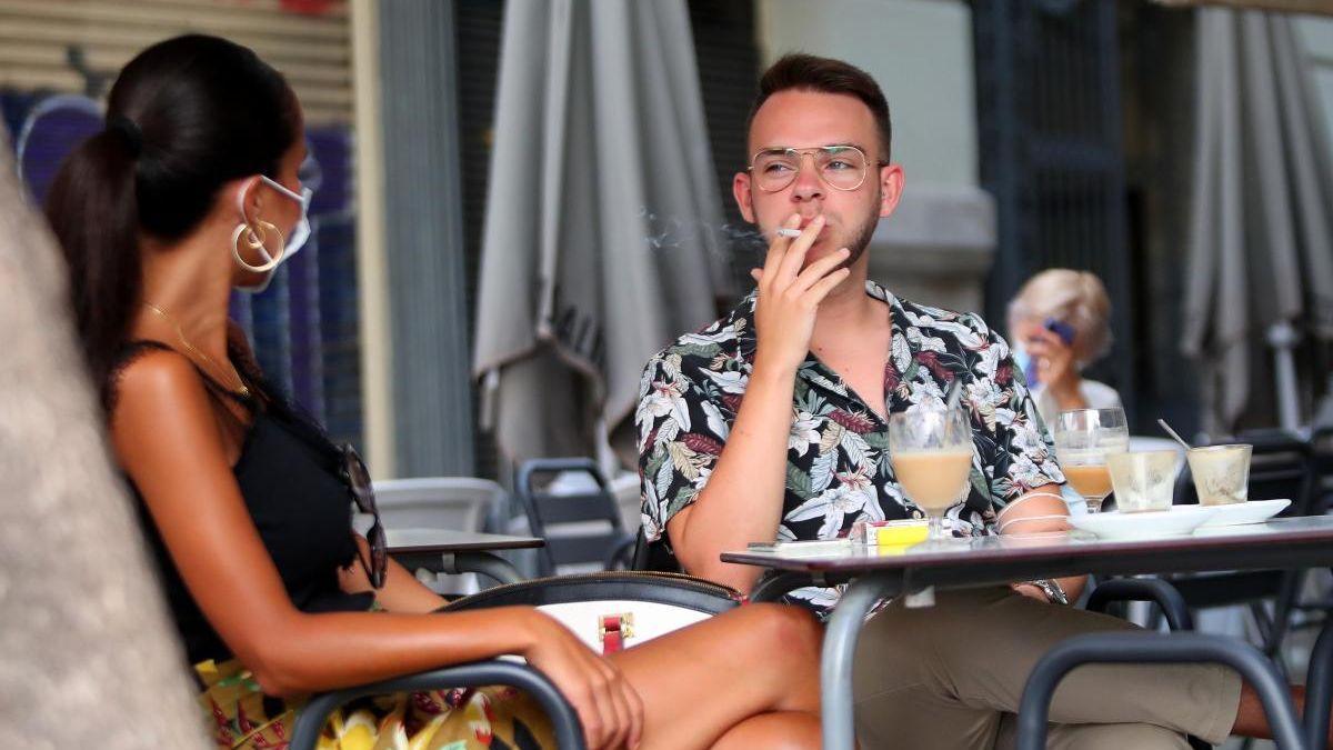Un hombre fuma en una terraza.