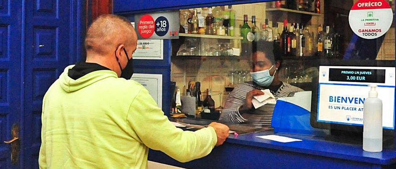 Yoselin Beltré sella boletos de lotería en el bar Carabela.