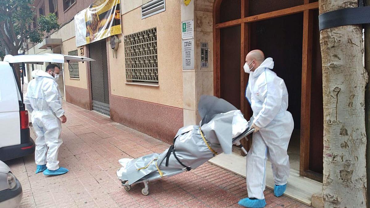 Operarios del retén fúnebre se llevan el cuerpo sin vida de Carlos Almiñana. | S.  SAPENA/M. PÉREZ