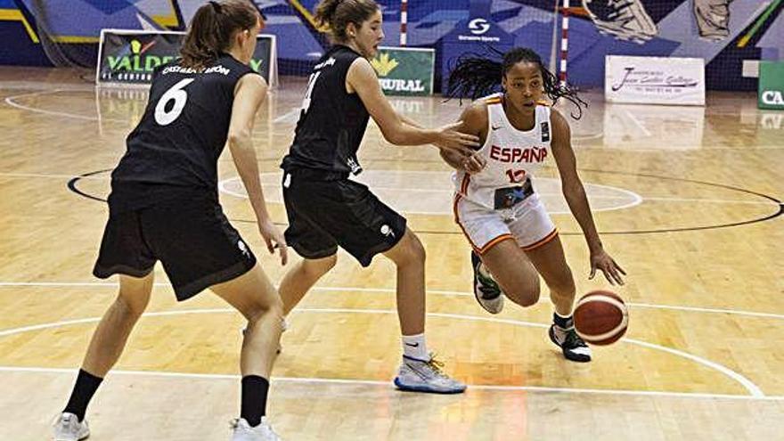 Noemi Ugochukwu, alero de la selección española, con el balón ante dos jugadoras de Castilla y León.