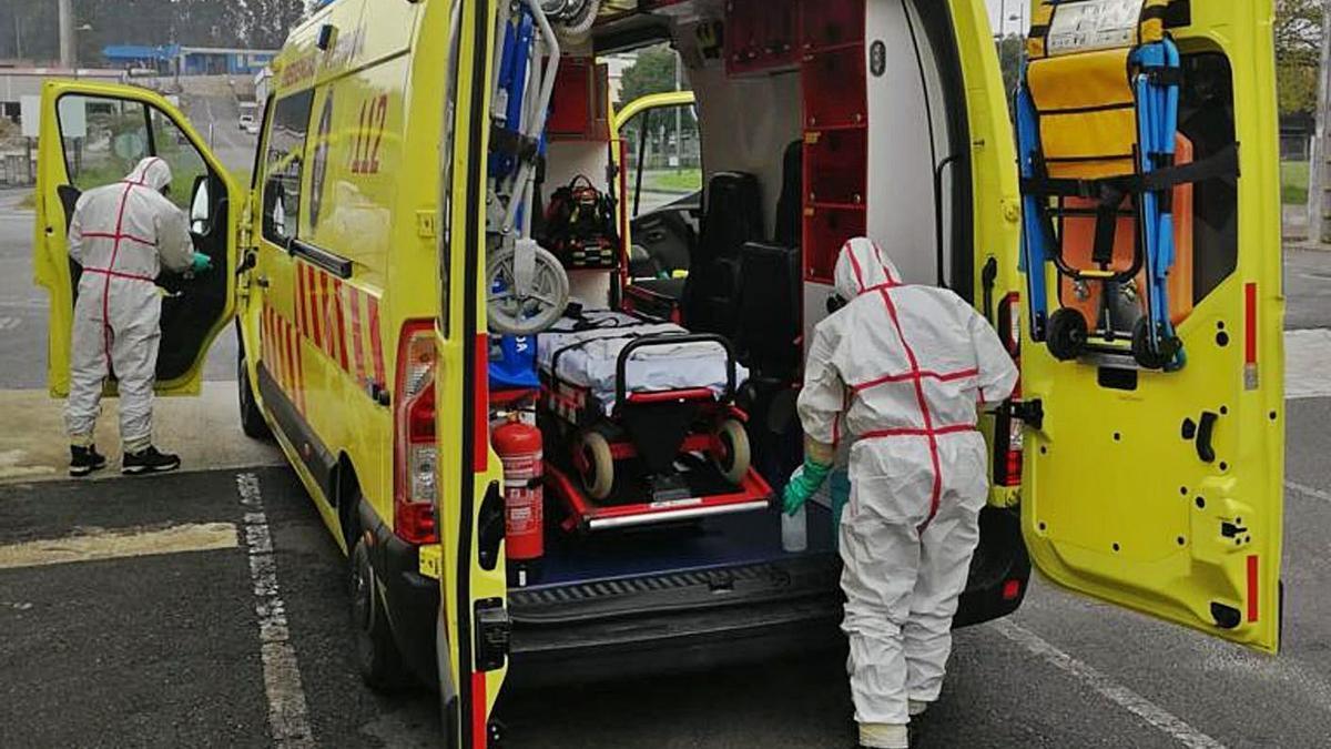 Personal de Emerxencias, con trajes de protección contra el COVID, limpiando la ambulancia. |  // EMERXENCIAS