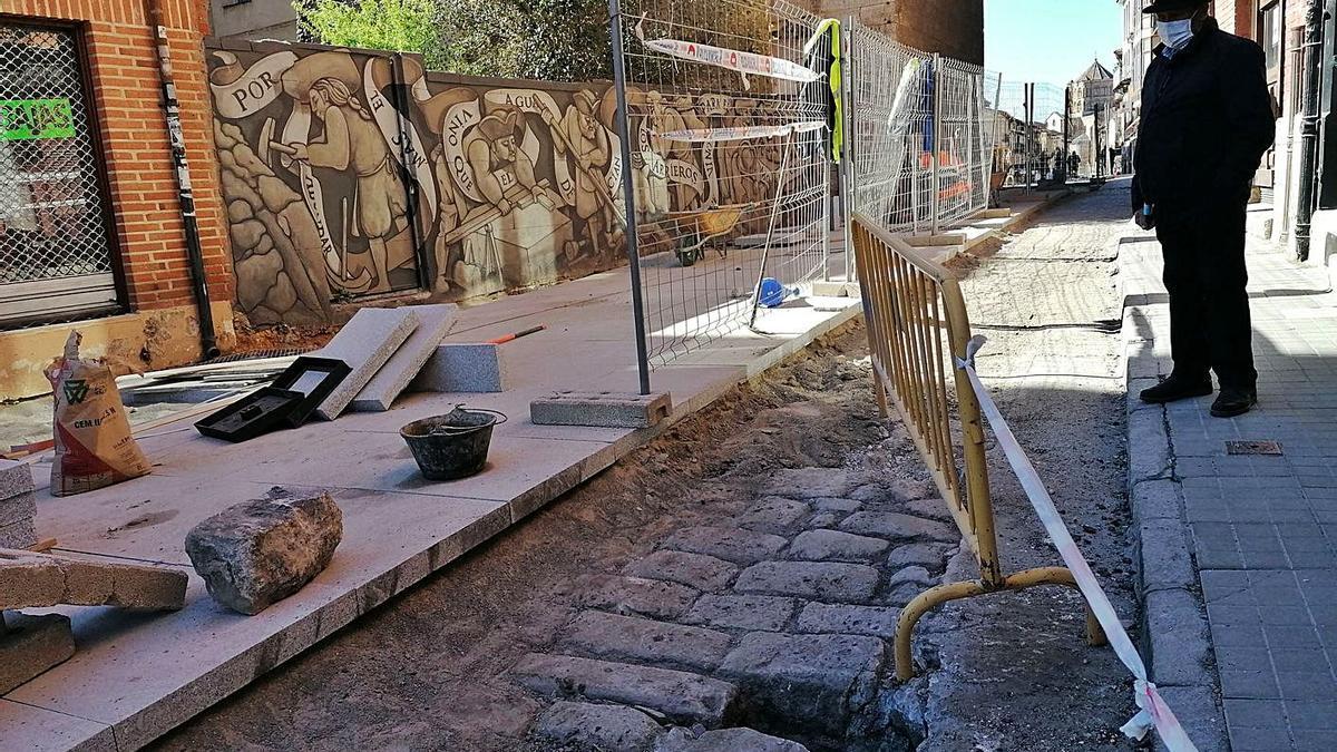Un vecino observa parte del antiguo pavimento que ha sido hallado en el entorno del Arco del Reloj. | M. J. C.
