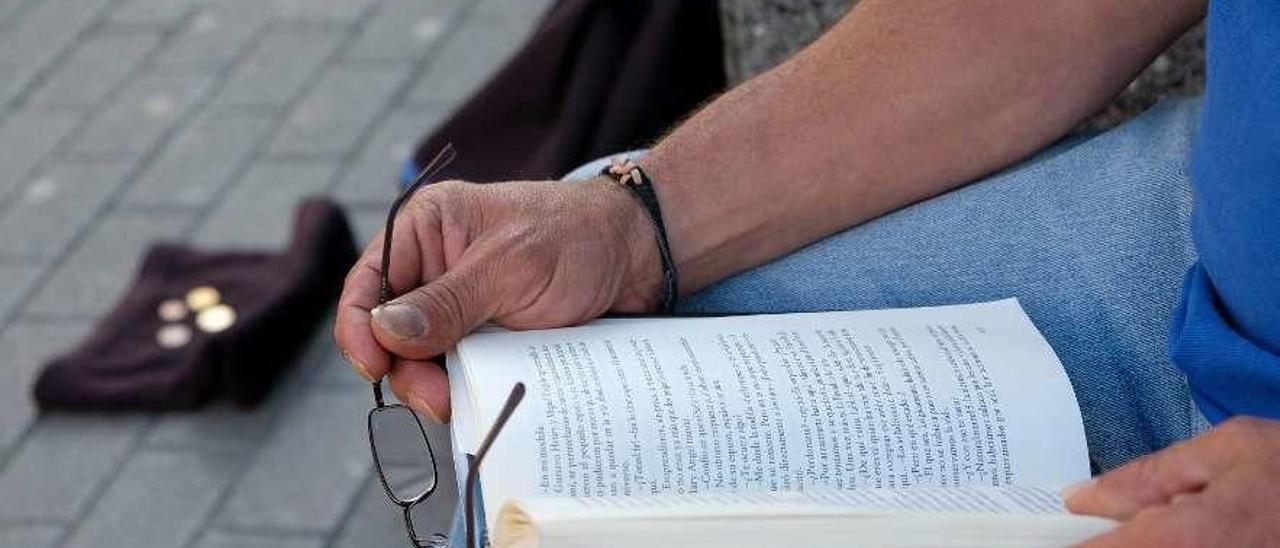 """Un mendigo leyendo el libro """"Icaro"""", en Mieres."""