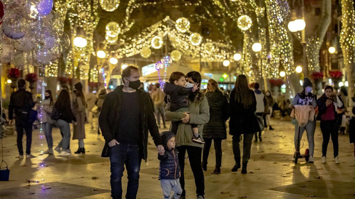 Familias paseando bajo las luces navideñas en el centro de Palma
