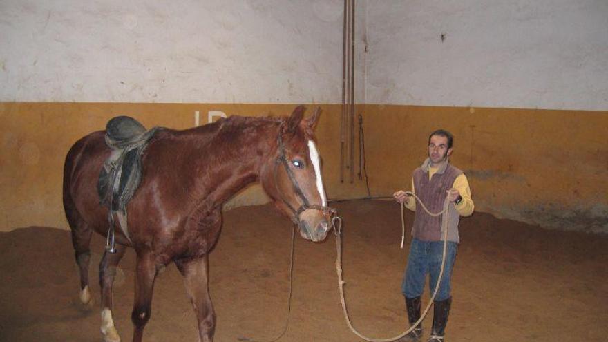 Pablo Gómez, propietario de los galgos, dando cuerda a un caballo