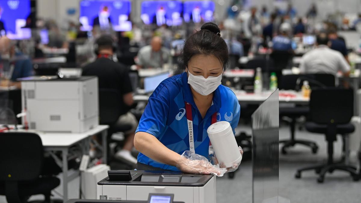 Una trabajadora limpia una impresora en el centro de prensa.
