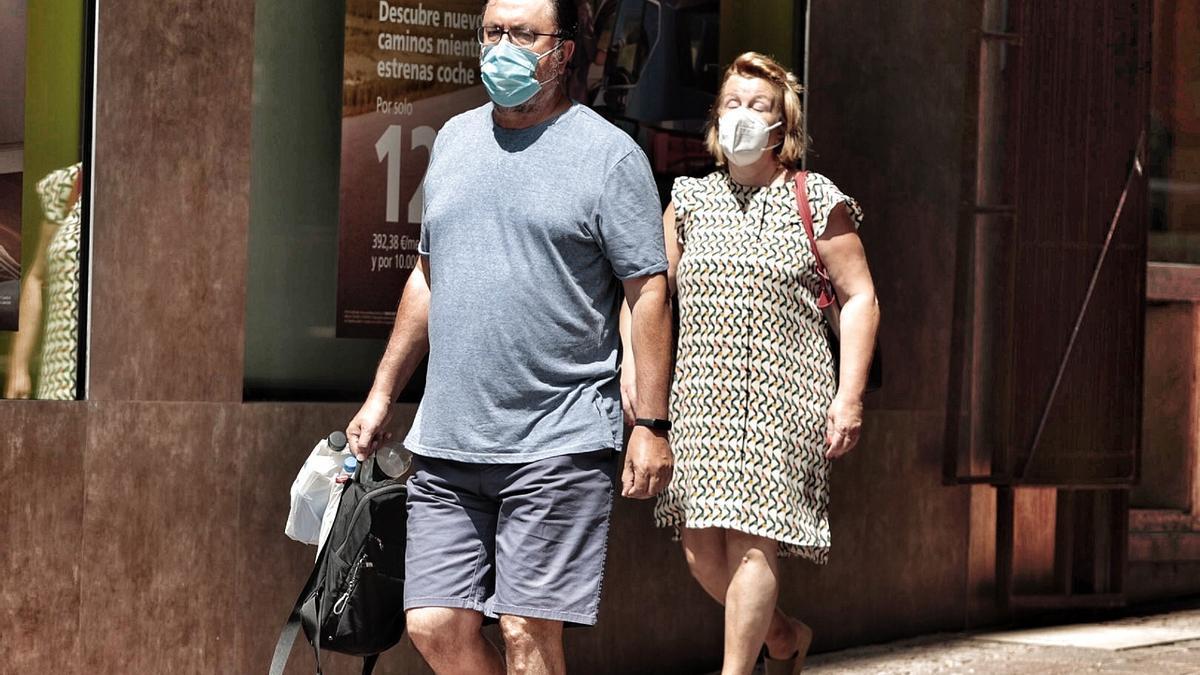 Dos personas con mascarilla caminan por las calles de Santa Cruz de Tenerife.