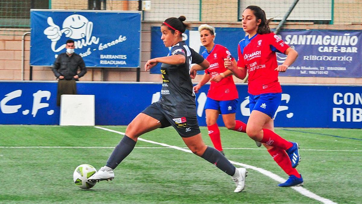 Elena, perseguida por dos futbolistas del Umia. |  // IÑAKI ABELLA