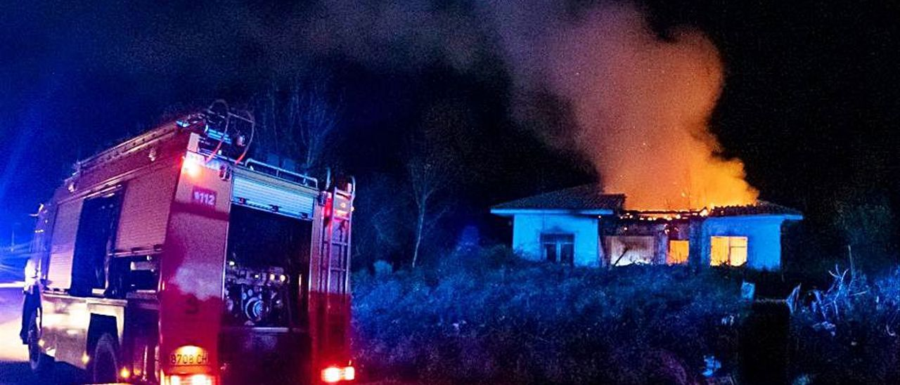 Los bomberos, ayer, interviniendo en la vivienda en llamas en Ribadesella.