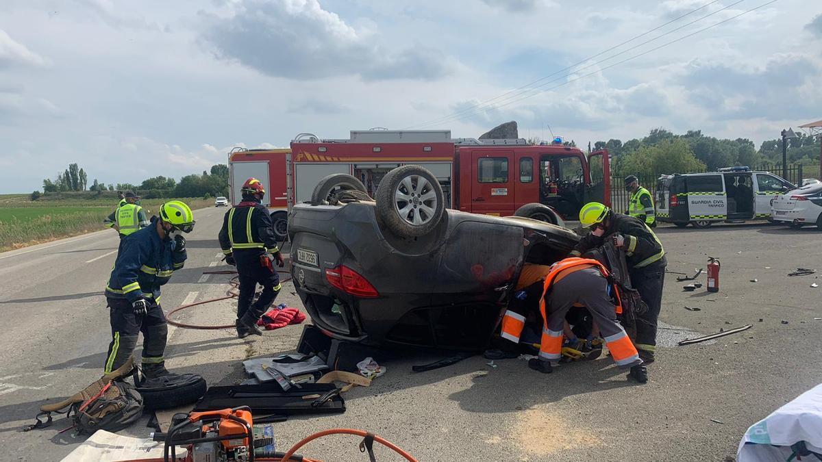 Los bomberos trabajan en el coche siniestrado durante el rescate del conductor.