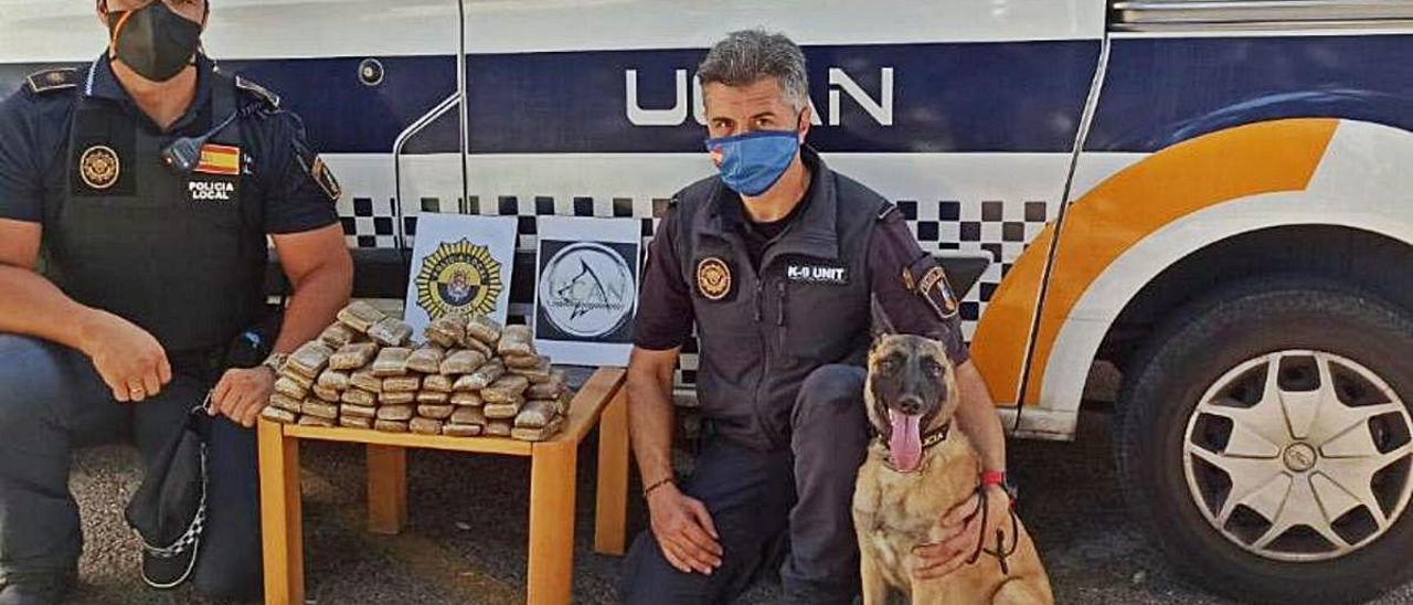 Agentes de la Unidad Canina de la Policía, con la droga y con el perro que la descubrió.