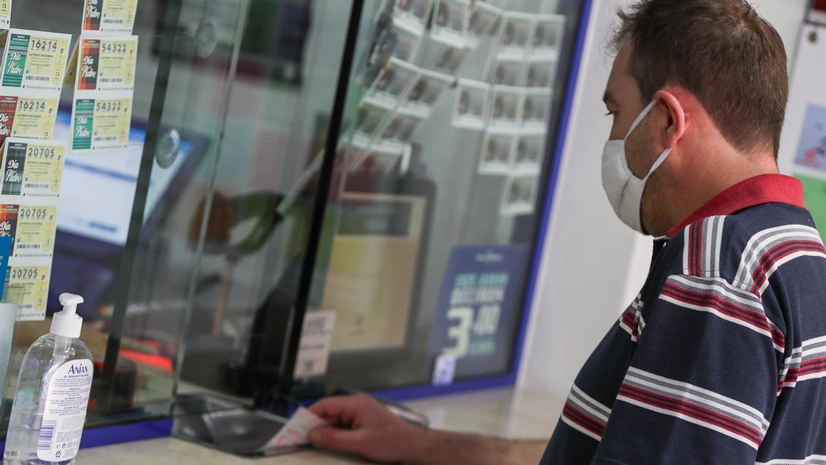 Un hombre compra lotería en una administración