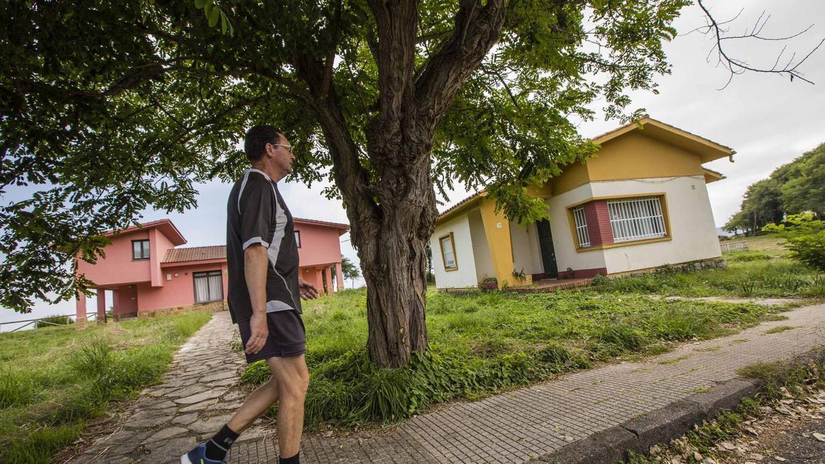Un hombre, paseando entre los chalés abandonados de la Ciudad de Vacaciones de Perlora
