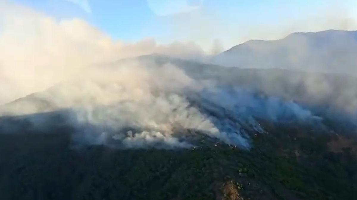 Imagen de uno de los helicópteros del Infoca sobrevolando la zona en llamas de Sierra Bermeja