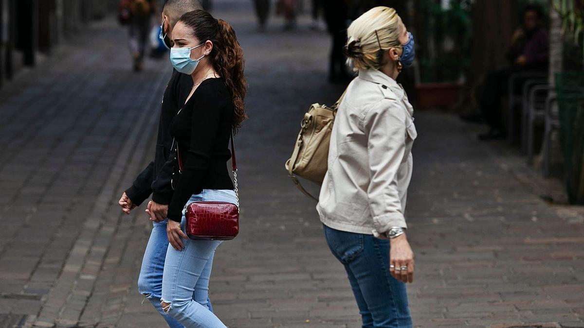 Una pareja y una mujer se cruzan en una calle de Santa Cruz en el día de ayer.