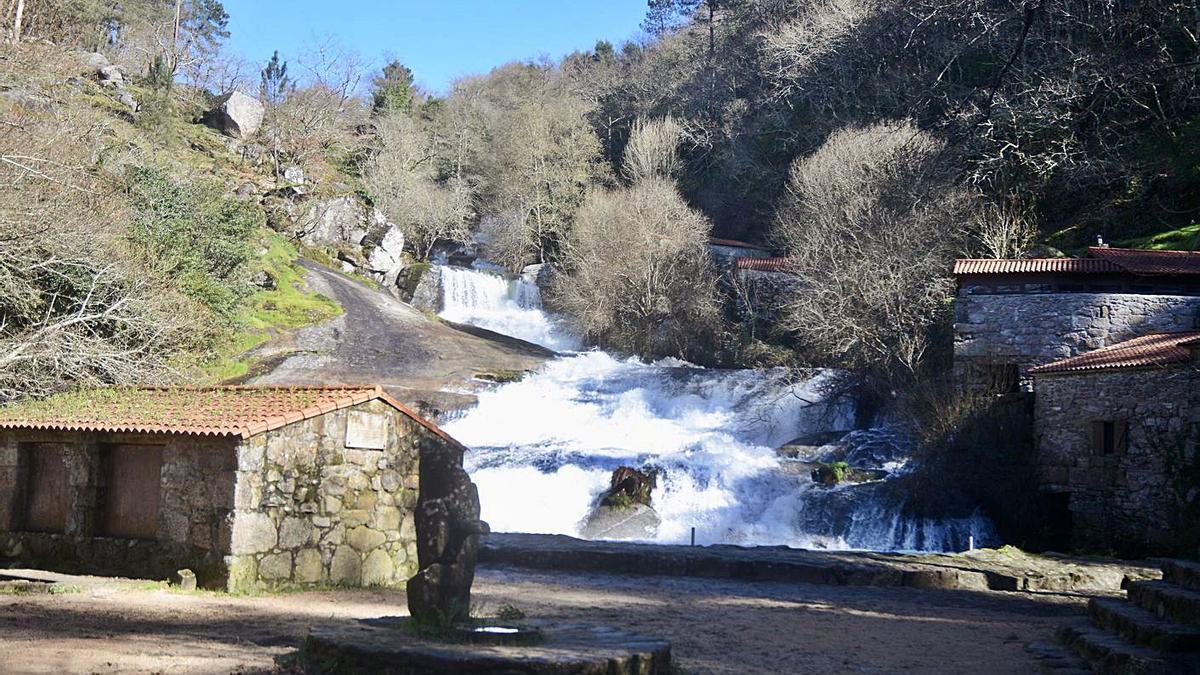 Arriba, estado que mostraba la cascada y los molinos de Barosa, ayer; a la izquierda, uno de los elementos en mal  estado.     // RAFA VÁZQUEZ